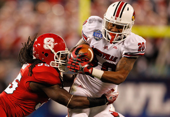 CHARLOTTE, NC - DECEMBER 27:  Victor Anderson #20 of the Louisville Cardinals is tackled by Terrell Manning #35 of the North Carolina State Wolfpack during their game at Bank of America Stadium on December 27, 2011 in Charlotte, North Carolina.  (Photo by