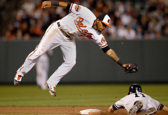 BALTIMORE, MD - APRIL 09: Brett Gardner #11 of the New York Yankees steals second base as Robert Andino #11 of the Baltimore Orioles catches the late throw during the seventh inning at Oriole Park at Camden Yards on April 9, 2012 in Baltimore, Maryland.
