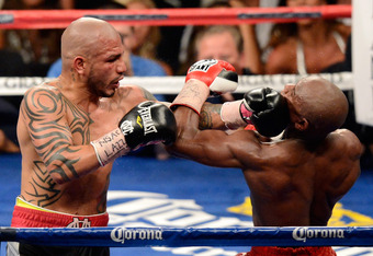 LAS VEGAS, NV - MAY 05:  Miguel Cotto (L) hits Floyd Mayweather Jr. during the 12th round of their WBA super welterweight title fight at the MGM Grand Garden Arena May 5, 2012 in Las Vegas, Nevada. Mayweather won by unanimous decision.  (Photo by Ethan Mi