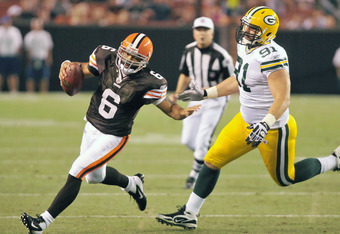 CLEVELAND, OH - AUGUST 13: Quarterback Seneca Wallace #6 of the Cleveland Browns runs from defensive end Lawrence Guy #91 of the Green Bay Packers during the third quarter at Cleveland Browns Stadium on August 13, 2011 in Cleveland, Ohio. The Browns defea