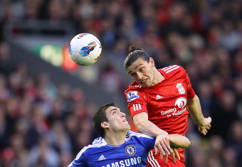 LIVERPOOL, ENGLAND - MAY 08: Andy Carroll of Liverpool wins the header ahead of Oriol Romeu of Chelsea during the Barclays Premier League match between Liverpool and Chelsea at Anfield on May 8, 2012 in Liverpool, England.  (Photo by Alex Livesey/Getty Im