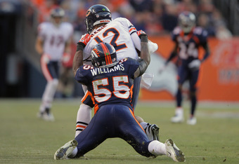 DENVER, CO - DECEMBER 11:  Quarterback Caleb Hanie #12 of the Chicago Bears is tackled by linebacker D.J. Williams #55 of the Denver Broncos at Sports Authority Field at Mile High on December 11, 2011 in Denver, Colorado. The Brocnos defeated the Bears 13