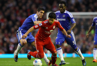LIVERPOOL, ENGLAND - MAY 08:  Oriol Romeu of Chelsea and Michael Essien of Chelsea close down Luis Suarez of Liverpool during the Barclays Premier League match between Liverpool and Chelsea at Anfield on May 8, 2012 in Liverpool, England.  (Photo by Alex