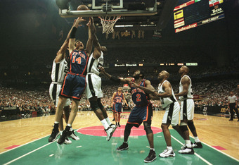 18 Jun 1999: Chris Dudley #14 of the New York Knicks gets hammered as he goes to the basket by Tim Duncan #21 and David Robinson #50 of the San Antonio Spurs during game two of the NBA Finals at the Alamodome in San Antonio, Texas. Mandatory Credit: Matth