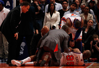 NEW YORK, NY - MAY 06:  Baron Davis #85 of the New York Knicks is tended to by the team medical staff and teammate Carmelo Anthony #7 after Davis injured his knee in the third quarter against the Miami Heat in Game Four of the Eastern Conference Quarterfi