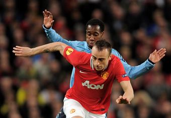 MANCHESTER, ENGLAND - FEBRUARY 23:  Dimitar Berbatov of Manchester United competes with Vurnon Anita of Ajax during the UEFA Europa League Round of 32 second leg match between Manchester United and AFC Ajax at Old Trafford on February 23, 2012 in Manchest