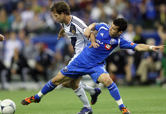 MONTREAL, CANADA - MAY 12:  Mike Magee #18 of the Los Angeles Galaxy and Felipe Martins #7 of the Montreal Impact battle for the ball during the MLS match at the Olympic Stadium on May 12, 2012 in Montreal, Quebec, Canada.  The game ended in a 1-1 tie.  (