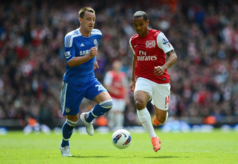 LONDON, ENGLAND - APRIL 21:  John Terry of Chelsea and Theo Walcott of Arsenal compete for the ball during the Barclays Premier League match between Arsenal and Chelsea at Emirates Stadium on April 21, 2012 in London, England.  (Photo by Mike Hewitt/Getty
