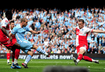 MANCHESTER, ENGLAND - MAY 13:  Pablo Zabaleta of Manchester City scores the opening goal past the outstretched Clint Hill of QPR during the Barclays Premier League match between Manchester City and Queens Park Rangers at the Etihad Stadium on May 13, 2012