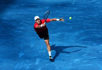 MADRID, SPAIN - MAY 12: Tomas Berdych of the Czech Republic jumps to play a backhand to Juan Martin Del Potro of Argentina in his semi final match during the Mutua Madrilena Madrid Open tennis tournament at the Caja Magica on May 12, 2012 in Madrid, Spain