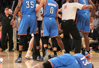 LOS ANGELES, CA - APRIL 22: James Harden #13 of the Oklahoma City Thunder lies on the floor after being hit by Metta World Peace #15 of the Los Angeles Lakers as referees separate Thunder and Lakers players at Staples Center on April 22, 2012 in Los Angel
