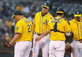 Bob Melvin (middle, in between Colon and Suzuki) has done well with pitching management this season, and should devote more attention to his infield.
