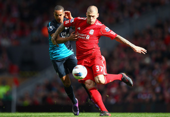 LIVERPOOL, ENGLAND - MARCH 03:  Theo Walcott of Arsenal and Martin Skrtel of Liverpool battle for the ball during the Barclays Premier League match between Liverpool and Arsenal at Anfield on March 3, 2012 in Liverpool, England.  (Photo by Clive Mason/Get
