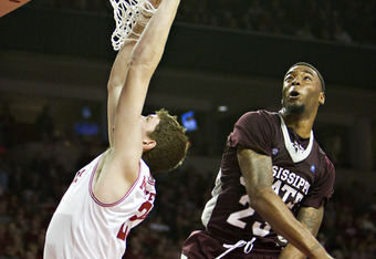 FAYETTEVILLE, AR - JANUARY 7:    Arnett Moultrie #23 of the Mississippi State Bulldogs blocks the shot but fouls Hunter Michelson #21 of the Arkansas Razorbacks at Bud Walton Arena on January 7, 2012 in Fayetteville, Arkansas.  The Razorbacks defeated the