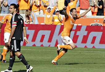 HOUSTON - MAY 12:  Brad Davis #11 of the Houston Dynamo celebrates his goal in the 67th minute against D.C. United  as Dwayne De Rosario #7 walks away at BBVA Compass Stadium on May 12, 2012 in Houston, Texas. Houston defeated D.C. United 1-0.  (Photo by