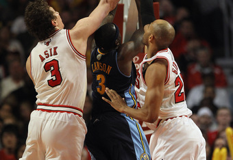 CHICAGO, IL - MARCH 26: Omer Asik #5 and Taj Gibson #22 of the Chicago Bulls try to block a shot by Ty Lawson #3 of the Denver Nuggets at the United Center on March 26, 2012 in Chicago, Illinois. The Nuggets defeated the Bulls 108-91. NOTE TO USER: User e
