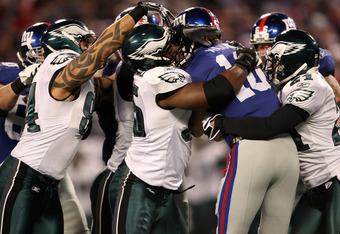 EAST RUTHERFORD, NJ - DECEMBER 13:  Eli Manning #10 of the New York Giants gets sacked by Joselio Hanson #21, Jason Babin #94 and  Victor Abiamiri #95 of the Philadelphia Eagles at Giants Stadium on December 13, 2009 in East Rutherford, New Jersey.  (Phot