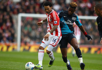 STOKE ON TRENT, ENGLAND - APRIL 28: Jermaine Pennant of Stoke City holds off a challenge from Alex Song of Arsenal during the Barclays Premier League match between Stoke City and Arsenal at Britannia Stadium on April 28, 2012 in Stoke on Trent, England.