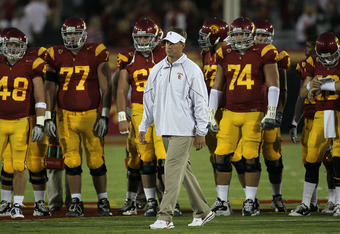 LOS ANGELES, CA - SEPTEMBER 11:  Head coach Lane Kiffin watches the USC Trojans warm up for their game with the Virginia Cavaliers at Los Angeles Memorial Coliseum on September 11, 2010 in Los Angeles, California.  (Photo by Stephen Dunn/Getty Images)
