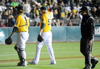 OAKLAND, CA - SEPTEMBER 16: Tevor Cahill #53 and Landon Powell #11 of the Oakland Athletics walk to the dugout after the lights go out against the Detroit Tigers in the fourth inning during an MLB baseball game at O.co Coliseum on September 16, 2011 in Oa