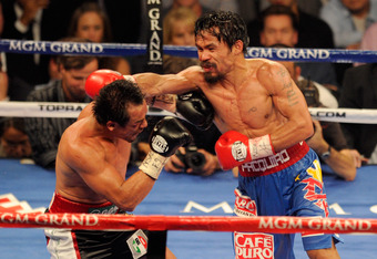 LAS VEGAS, NV - NOVEMBER 12:  (R-L) Manny Pacquiao throws a right to the head of Juan Manuel Marquez during the WBO world welterweight title fight at the MGM Grand Garden Arena on November 12, 2011 in Las Vegas, Nevada.  (Photo by Ethan Miller/Getty Image