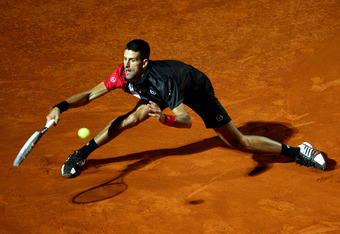 ROME, ITALY - MAY 15:  Novak Djokovic of Serbia stretches to play a forehand against  Bernard Tomic of Australia  in their second round match during day four of the Internazionali BNL d'Italia 2012 at the Foro Italico Tennis Centre  on May 15, 2012 in Rom