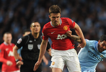 MANCHESTER, ENGLAND - APRIL 30: Michael Carrick of Manchester United in action with Carlos Tevez of Manchester City during the Barclays Premier League match between Manchester City and Manchester United at Etihad Stadium on April 30, 2012 in Manchester, E