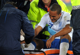 BASEL, SWITZERLAND - SEPTEMBER 07:  Theo Walcott of England grimaces as he receives treatment before being taken off injured during the EURO 2012 Qualifier between Switzerland and England at St Jakob Park on September 7, 2010 in Basel, Switzerland.  (Phot