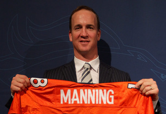 ENGLEWOOD, CO - MARCH 20:  Quarterback Peyton Manning poses with his uniform after the news conference announcing his contract with the Denver Broncos in the team meeting room at the Paul D. Bowlen Memorial Broncos Centre on March 20, 2012 in Englewood, C