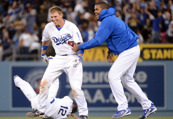 AJ Ellis, Justin Sellers (12) and Kenley Jansen celebrate the Dodgers' walk-off win.