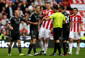 STOKE ON TRENT, ENGLAND - SEPTEMBER 10:  Craig Bellamy of Liverpool (L) argues with referee Mark Clattenburg during the Barclays Premier League match between Stoke City and Liverpool at Britannia Stadium on September 10, 2011 in Stoke on Trent, England.