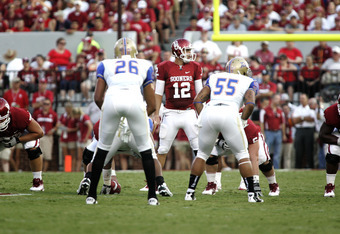 NORMAN, OK - SEPTEMBER 03:  Quarterback Landry Jones #12 of the Oklahoma Sooners looks at the line of scrimmage in the first half of the game against the Tulsa Hurricanes September 3, 2011 at Gaylord Family-Oklahoma Memorial Stadium in Norman, Oklahoma.