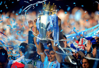 MANCHESTER, ENGLAND - MAY 13:  Scorer of the matchwinning goal Sergio Aguero of Manchester City celebrates with the trophy during the Barclays Premier League match between Manchester City and Queens Park Rangers at the Etihad Stadium on May 13, 2012 in Ma