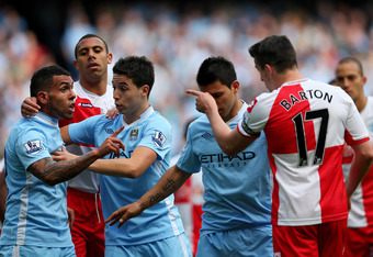 MANCHESTER, ENGLAND - MAY 13:  Carlos Tevez of Manchester City clashes with Joey Barton of QPR after being fouled during the Barclays Premier League match between Manchester City and Queens Park Rangers at the Etihad Stadium on May 13, 2012 in Manchester,