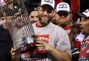 ST LOUIS, MO - OCTOBER 28:  Lance Berkman #12 of the St. Louis Cardinals celebrates with the World Series trophy after defeating the Texas Rangers 6-2 in Game Seven of the MLB World Series at Busch Stadium on October 28, 2011 in St Louis, Missouri.  (Phot
