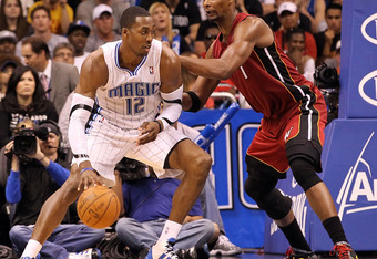 ORLANDO, FL - MARCH 13:  Dwight Howard #12 of the Orlando Magic is guarded by Chris Bosh #1 of the Miami Heat during the game at Amway Center on March 13, 2012 in Orlando, Florida.  NOTE TO USER: User expressly acknowledges and agrees that, by downloading