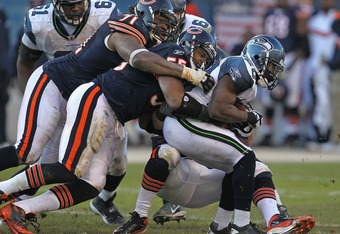 CHICAGO, IL - DECEMBER 18:  Justin Forsett #20 of the Seattle Seahawks is hit by (L-R) Israel Idonije #71, Lance Briggs #55 and Brian Urlacher #54 of the Chicago Bears at Soldier Field on December18, 2011 in Chicago, Illinois. The Seahawks defeated the Be