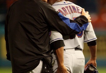 MIAMI - APRIL 01:  Starting pitcher Pedro Martinez #45 of the New York Mets talks with a trainer after a hamstring injury in the fourth inning against the Florida Marlins at Dolphin Stadium on April 1, 2008 in Miami, Florida.  (Photo by Doug Benc/Getty Im