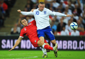 LONDON, ENGLAND - SEPTEMBER 06:  Wayne Rooney (R) of England is tackled by Darcy Blake (L) of Wales during the UEFA EURO 2012 group G qualifying match between England and Wales at Wembley Stadium  on September 6, 2011 in London, England.  (Photo by David