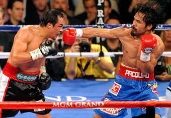 LAS VEGAS, NV - NOVEMBER 12:  Manny Pacquiao (R) throws a right at Juan Manuel Marquez during the seventh round of their WBO world welterweight title fight at the MGM Grand Garden Arena November 12, 2011 in Las Vegas, Nevada. Pacquiao retained his title w