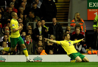 LIVERPOOL, ENGLAND - OCTOBER 22:  Grant Holt of Norwich City celebrates scoring his team's first goal during the Barclays Premier League match between Liverpool and Norwich City at Anfield on October 22, 2011 in Liverpool, England.  (Photo by Richard Heat