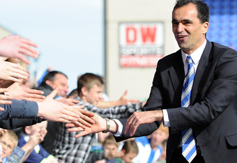 WIGAN, ENGLAND - MAY 13:  Wigan Athletic manager Roberto Martinez shakes hands with the supporters following the Barclays Premier League match between Wigan Athletic and Wolverhampton Wanderers at DW Stadium on May 13, 2012 in Wigan, England.  (Photo by C