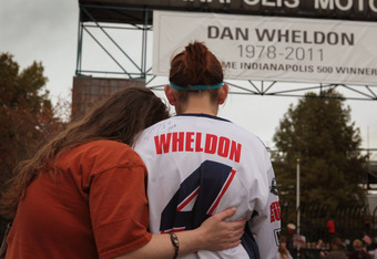 INDIANAPOLIS, IN - OCTOBER 17:  Deann Klotzsche (L) and Katie Mitchell comfort each other as they view a memorial to two-time Indianapolis 500 winner Dan Wheldon at the gate of the Indianapolis Motor Speedway on October 17, 2011 in Indianapolis, Indiana.