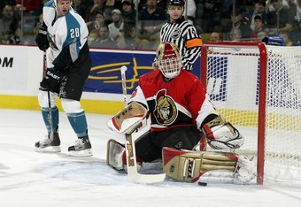 OTTAWA - JANUARY 12:  Dominik Hasek #39 of the Ottawa Senators makes a pad save as Nils Ekman #28 of the San Jose Sharks looks on during first period action on January 12, 2006 at the Corel Centre in Ottawa, Ontario, Canada.  (Photo by Phillip MacCallum/G