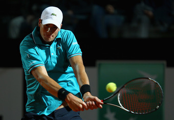 ROME, ITALY - MAY 14:  John Isner of the USA plays a backhand against Philipp Kohlschreiber of Germany  in their first round match during day three of the Internazionali BNL d'Italia 2012  at the Foro Italico Tennis Centre on May 14, 2012 in Rome, Italy.