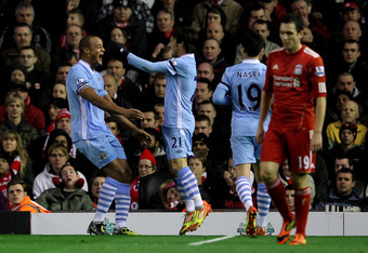 LIVERPOOL, ENGLAND - NOVEMBER 27:  Vincent Kompany of Manchester City celebrates scoring the opening goal with team mate David Silva (R) during the Barclays Premier League match between Liverpool and Manchester City at Anfield on November 27, 2011 in Live