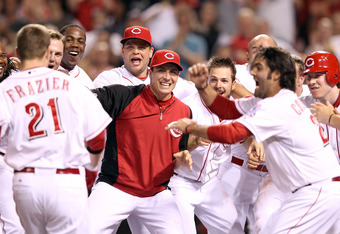 CINCINNATI, OH - MAY 23:  Todd Frazier #21 of the Cincinnati Reds appraoches his celebrating teammates after hitting a game winning home run in the 9th inning during the game against the Atlanta Braves at Great American Ball Park on May 23, 2012 in Cincin