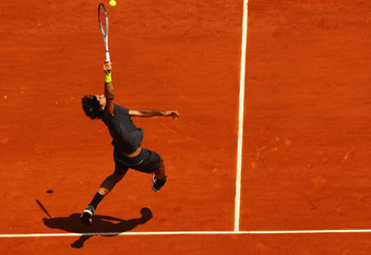 PARIS, FRANCE - MAY 28:  Roger Federer of Switzerland leaps to hit the ball in the men's singles first round match between Roger Federer of Switzerland and Tobias Kamke of Germany during day two of the French Open at Roland Garros on May 28, 2012 in Paris