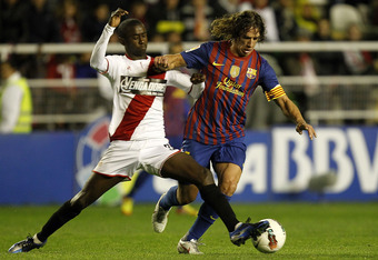 MADRID, SPAIN - APRIL 29:  Carles Puyol of FC Barcelona fights for the ball with Diamanka of Rayo Vallecano during the La Liga match between Rayo Vallecano and FC Barcelona at Estadio Teresa Rivero on April 29, 2012 in Madrid, Spain.  (Photo by Angel Mart