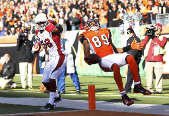 CINCINNATI, OH - DECEMBER 24: Jerome Simpson #89 of the Cincinnati Bengals jumps over Daryl Washington #58 of the Arizona Cardinals for a 19-yard touchdown during first half action at Paul Brown Stadium on December 24, 2011 in Cincinnati, Ohio. (Photo by